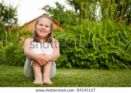 Backyard portrait of smiling child (nine years old girl) sitting on grass