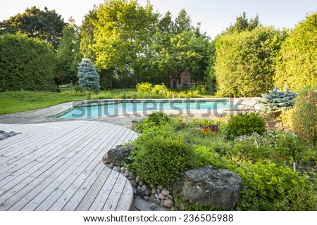 Backyard rock garden with outdoor inground residential swimming pool, curved wooden deck and stone patio - stock photo