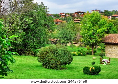 Backyard with Decorative Garden and Outdoors Furniture. Bulgarian Summer Landscape. - stock photo