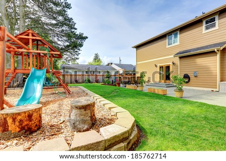 Backyard with patio area and playground for kids - stock photo