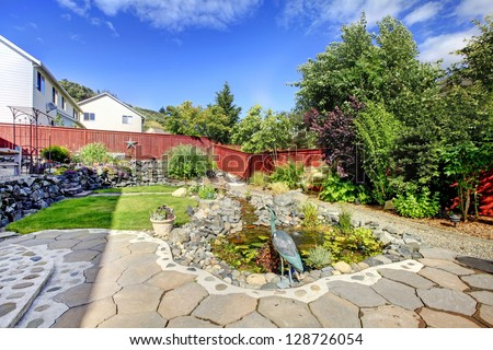 Backyard with porch, pond and rocks and red fence.