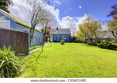 Backyard with small blue house and bright green spring grass. American house build in 1942. - stock photo