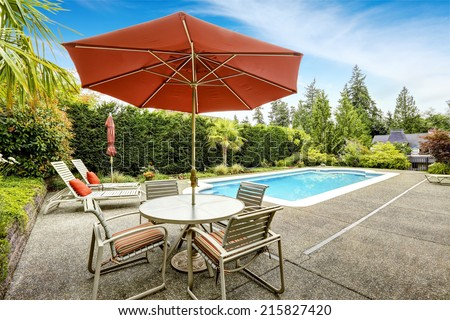 Backyard with swimming pool, deck chairs and patio table with umbrella - stock photo