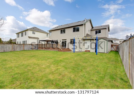 Backyard with typical American house, green grass and fence. - stock photo
