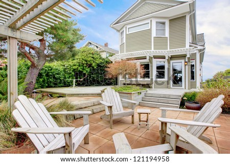 Backyard with white chairs and tall old home during spring. - stock photo