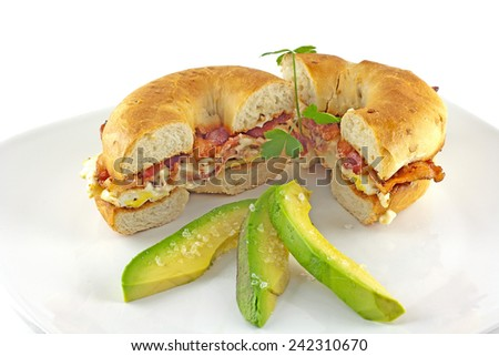Bacon and egg sandwich on an onion bagel with avocado slices