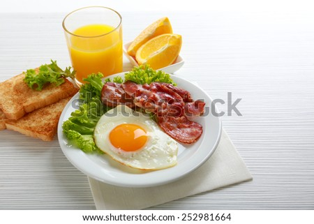 Bacon and eggs on color wooden table background - stock photo