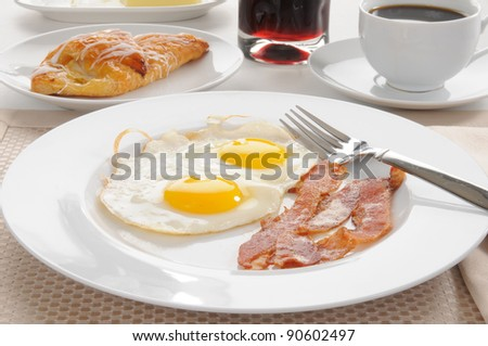 Bacon and eggs with a Danish pastry, grape juice and coffee