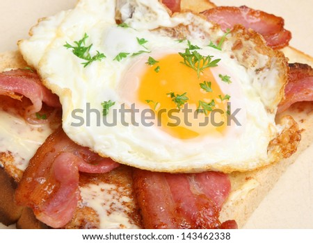 Bacon and fried egg on toast. - stock photo