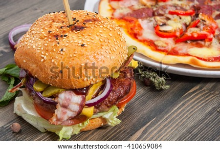 bacon cheese burger with beef patty tomato onion and pizza on a wooden table - stock photo