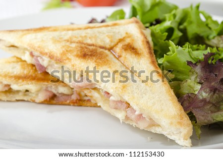 Bacon & Cheese Toastie served with salad on a white background. Close up.