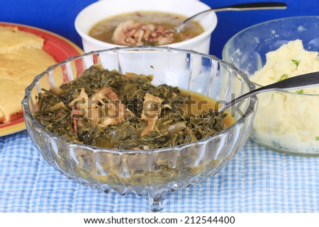 Bacon fat in Collard Greens in clear glass bowl surrounded by soul food dishes on blue gingham.  Black-eyed peas; mashed potatoes; corn bread. - stock photo