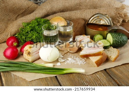 Bacon, fresh vegetables, boiled egg and bread on paper, glasses with vodka on wooden background. Village breakfast concept.