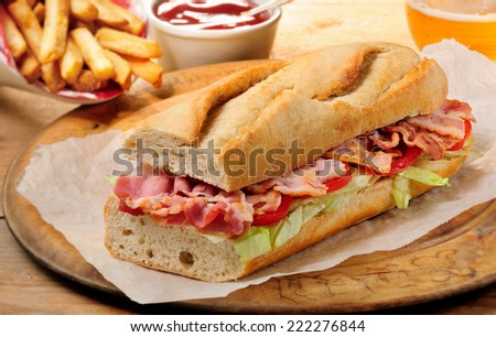 Bacon, lettuce and tomato (BLT) submarine sandwich. French fries, tomato ketchup and glass of beer on background. - stock photo