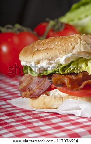 Bacon, lettuce and tomato sandwich or BLT freshly made, with vibrant, healthy colours on a red gingham tablecloth with whole tomatoes and lettuce in the background