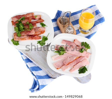 Bacon on plates on napkin on board isolated on white