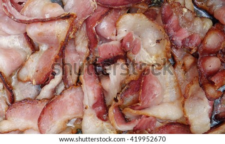 Bacon Pork Meat Frying Background - Close up top view of greasy bacon strips cooking in a pan, greasy pork meat background. - stock photo