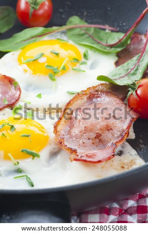 Bacon rashers with fried eggs, tomato, baby chard and chopped pea shoots. All in a frying pan. New version. - stock photo