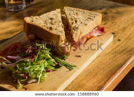 Bacon sandwich on thick wholemeal granary bread on wooden platter on pub lunch table - stock photo