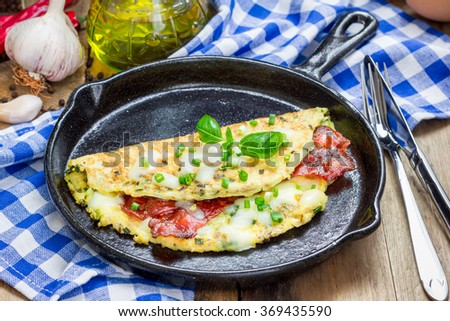 Bacon stuffed omelette on a iron cast pan - stock photo