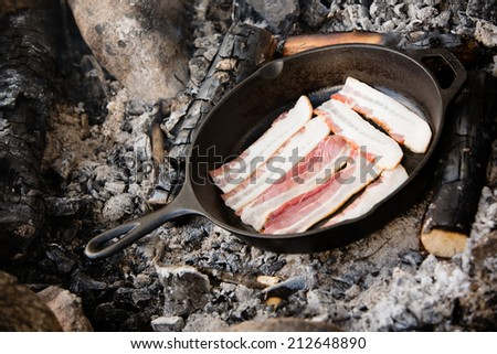 Bacon - This is a shot of bacon being cooked over warm coals from a campfire. - stock photo