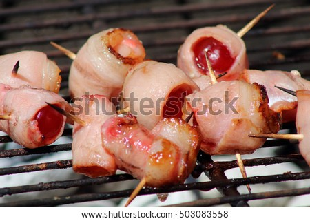 Bacon wrapped cherry skewers simmer on a barbecue.