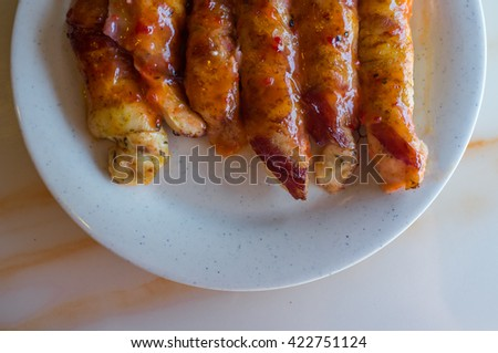 Bacon wrapped chicken tenders in honey glaze arranged on plate - stock photo