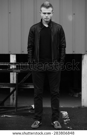 Bad boy concept. Portrait of brutal young man with short hair wearing black jacket, jeans and posing over urban background. Hipster style. Outdoor shot - stock photo