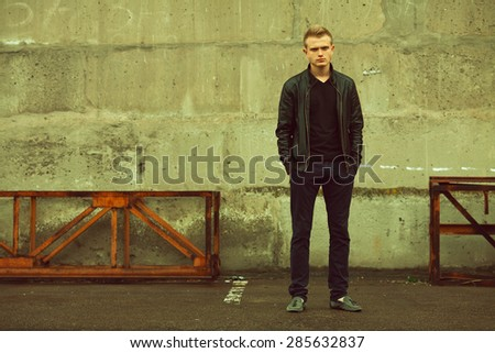 Bad boy concept. Portrait of brutal young man with short hair wearing black jacket, jeans and posing over urban background. Hands in pockets. Hipster style. Copy-space. Outdoor shot