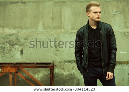 Bad boy concept. Portrait of brutal young man with short hair wearing black jacket, jeans and posing over urban background. Hand in pockets. Hipster style. Copy-space. Outdoor shot