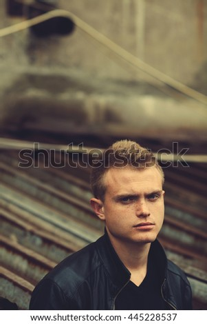Bad boy concept. Portrait of brutal young man with short hair wearing black leather jacket, posing over urban corrugated background. Copy-space. Outdoor shot