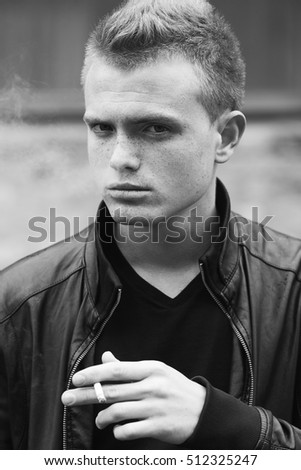 Bad boy concept. Portrait of brutal young man with short hair wearing black leather jacket, posing over urban background and smoking. Close up. Outdoor shot