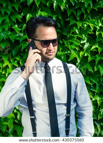Bad business talk. Handsome young man talking on the mobile phone and smiling while standing against decorative trees background.Good looking casual office worker talking on mobile phone - stock photo