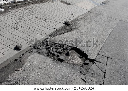Bad chuckhole and rubbles in asphalt road damaged street in Warsaw, Poland, horizontal orientation, nobody.