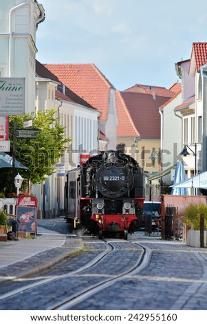 "BAD DOBERAN, GERMANY - AUGUST 24, 2014: The steam train ""Molli"" fully loaded with tourists on its way through the streets of Bad Doberan  - stock photo"