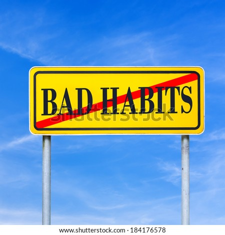 Bad Habits prohibited - conceptual image with the words Bad Habits crossed through in red on a yellow traffic sign against a sunny clear blue sky. - stock photo