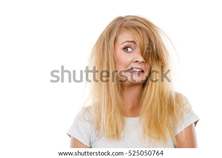 Bad hairstyle concept. Crazy, mad blonde woman with messy hair looking stressed out. Studio shot on white background.