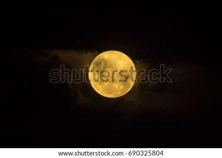 Bad moon rising. Yellow moon with clouds