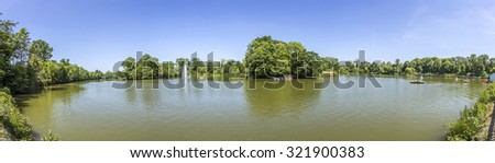 BAD NAUHEIM, GERMANY - JUNE 4, 2015: people enjoy the boat trip at the lake in Bad Nauheims Kurpark. The Kurpark was planned by architect Heinrich Siesmayers.