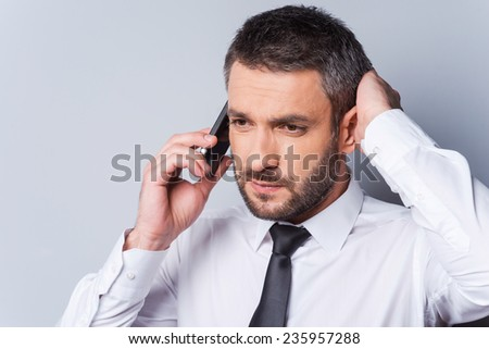 Bad news. Frustrated mature man in shirt and tie talking on the mobile phone and holding hand in hair while standing against grey background - stock photo