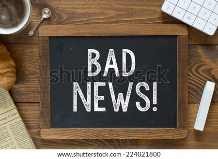 Bad News handwritten with white chalk on a blackboard on a wooden background