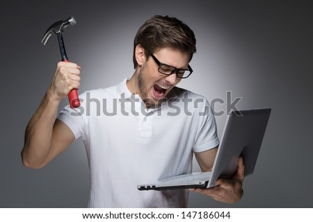 Bad news. Portrait of furious young men trying to break a laptop by hummer while standing isolated on grey - stock photo