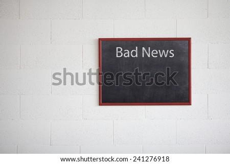 Bad news, writing on chalkboard - stock photo