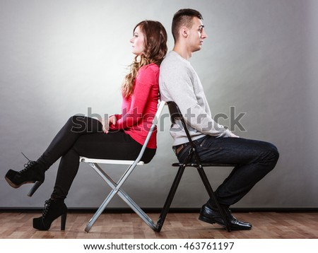 Bad relationship concept. Man and woman in disagreement. Young couple after quarrel sitting on chairs back to back