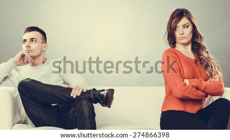Bad relationship concept. Man and woman in disagreement. Young couple after quarrel sitting on sofa - stock photo