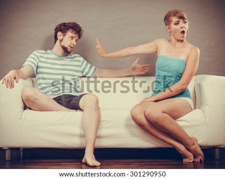 Bad relationship concept. Man and woman in disagreement. Young couple sitting on couch at home having quarrel, offended wife and unhappy husband - stock photo