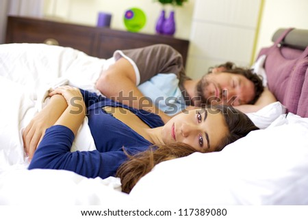 Bad relationship young woman depressed about sleeping boyfriend - stock photo