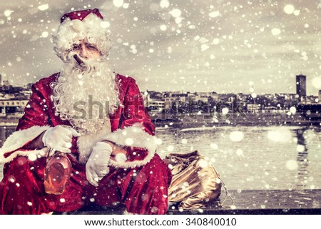 Bad Santa holding bottle of brandy and cigar in his mouth - stock photo