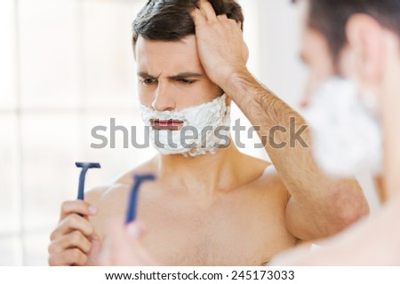Bad shaver. Rear view of frustrated young shirtless man with shaving cream on his face holding a razor and looking at it while standing in front of the mirror