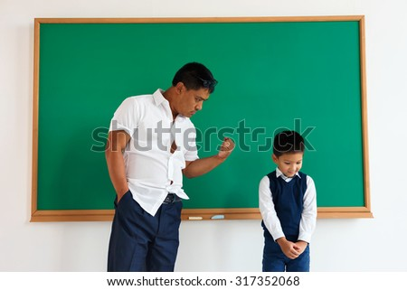 Bad teacher, bad education /  learning in the classroom / photo of teen school Chinese boy /  school theme
